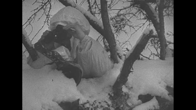 [VO Spanish language throughout] High angle view of a long line of Soviets on snow / VS Soviets and weaponry on large sleighs pulled by reindeer / VS...