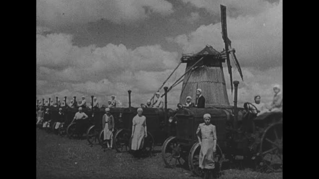 [VO Spanish language throughout] Russian men examine rows of tractors in snow / women stand next to machines with windmill behind them / woman hand...
