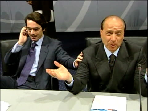 spanish prime minister jose maria aznar and italian prime minister silvio berlusconi sit at table laughing at eu summit copenhagen 13 dec 02 - global communications stock videos & royalty-free footage
