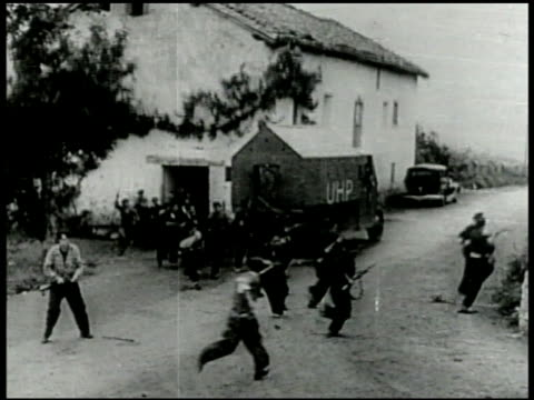 stockvideo's en b-roll-footage met spanish republican soldiers holding guns running out of building across street running up rocky hill. - 1936