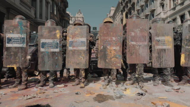 Spanish riot police stand in a line after being doused with color powder used in Holi festivals by protestors on September 29 2018 in Barcelona Spain...