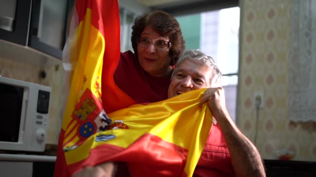 Spanish senior couple fan watching soccer game at home