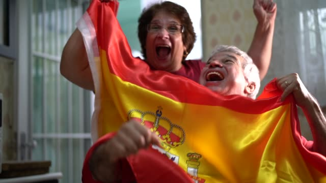 spanish senior couple fan watching soccer game at home - fan enthusiast stock videos & royalty-free footage