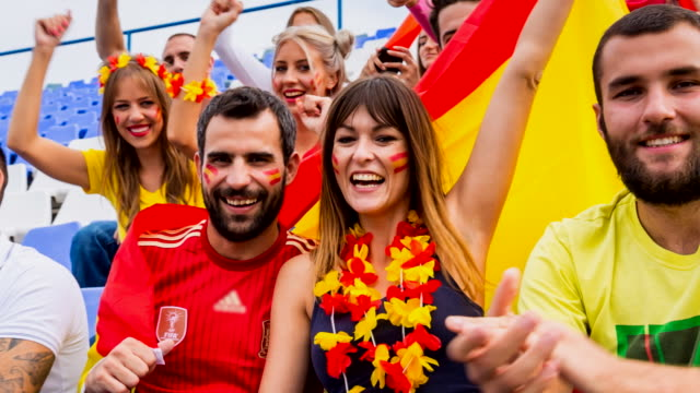 cu spanish sport fans at soccer stadium, cheering into camera - spanish flag stock videos and b-roll footage