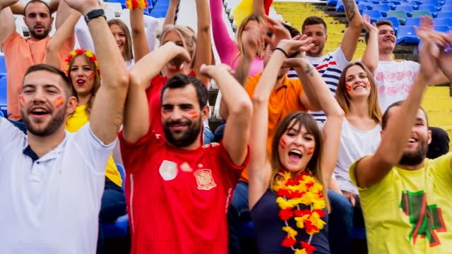 ms spanish sport fans celebrating at soccer stadium - スペイン国旗点の映像素材/bロール