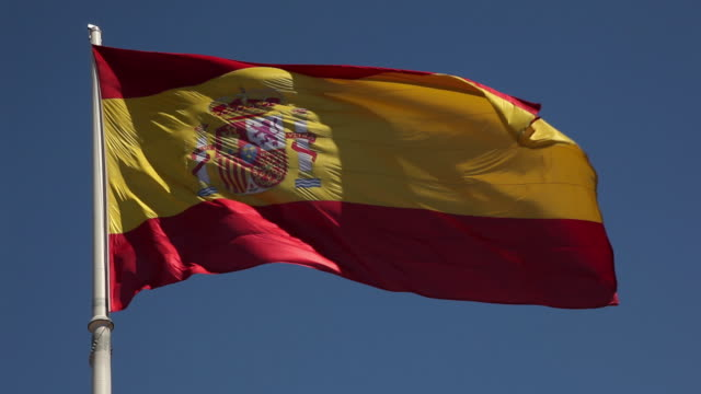 ms spanish swaying on wind against blue sky / madrid, spain - spanish flag stock videos and b-roll footage