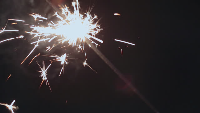 a sparkler crackles and pops with light in the night air. - life events stock videos & royalty-free footage