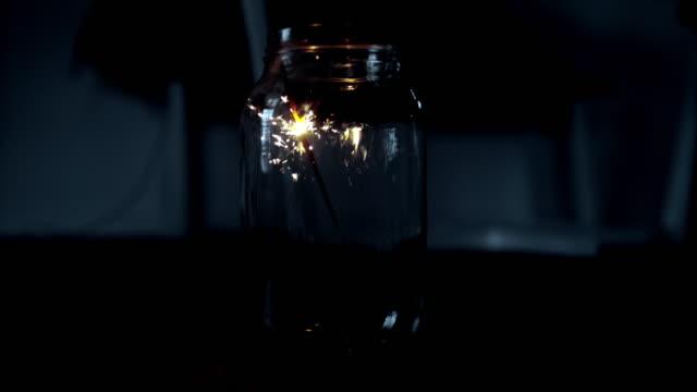 ms super slow motion sparkler firework sparking inside glass jar - advent stock videos & royalty-free footage