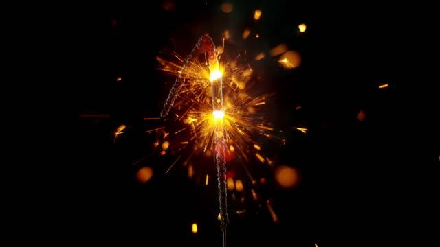 vídeos de stock, filmes e b-roll de slo mo ld sparkler moldado como o 'número 1' emitindo faíscas e chamas enquanto queima - número 1