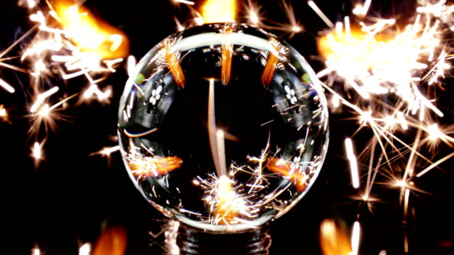 sparklers burning behind glass ball - crystal ball stock videos & royalty-free footage
