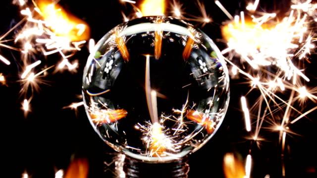 vídeos de stock e filmes b-roll de sparklers burning behind glass ball - vidro