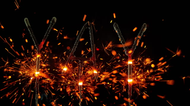 vídeos de stock e filmes b-roll de slo mo ld sparklers shaped as the exclamation 'yay' emitting sparks - escrita ocidental
