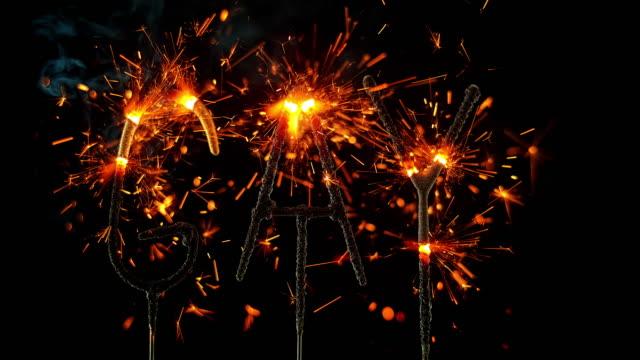 vídeos de stock e filmes b-roll de slo mo ld sparklers shaped as the word 'gay' emitting sparks - escrita ocidental