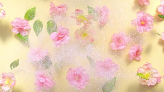 sparkling glitter and silk cherry blossoms with leaves, exploding towards camera in slow motion on light yellow background, glittering bokeh - coloured background stock videos & royalty-free footage