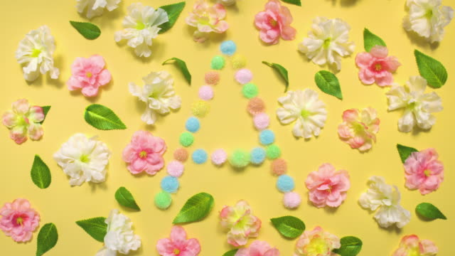 Sparkling Letter A- exploding multi pastel colored glitter powder surrounded by cherry blossoms and leaves on pastel yellow background