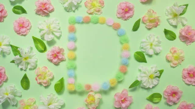 Sparkling Letter D- exploding multi pastel colored glitter powder surrounded by cherry blossoms and leaves on pastel green background