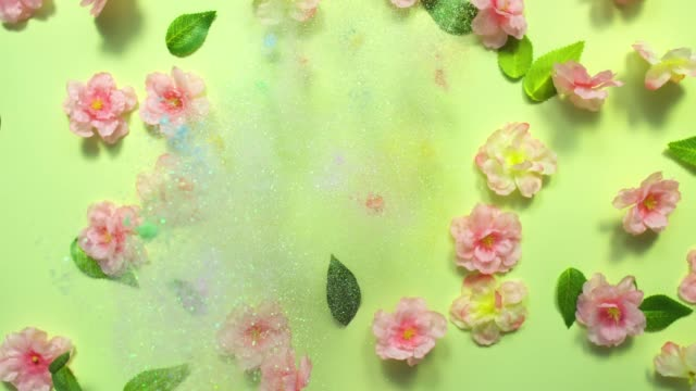 Sparkling Letter F- exploding multi pastel colored glitter powder surrounded by silk cherry blossoms and leaves on light green background