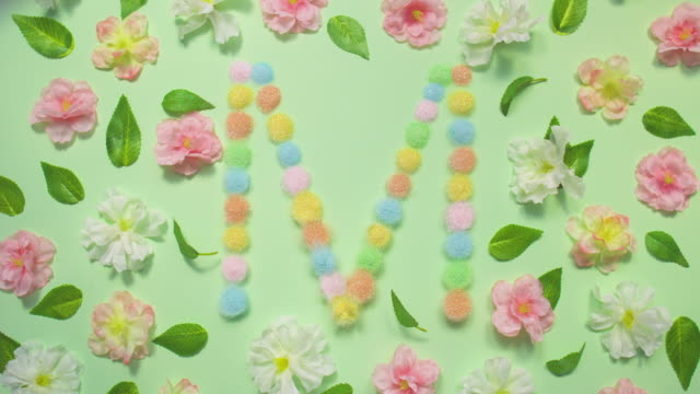 Sparkling Letter M- exploding multi pastel colored glitter powder surrounded by cherry blossoms and leaves on pastel green background