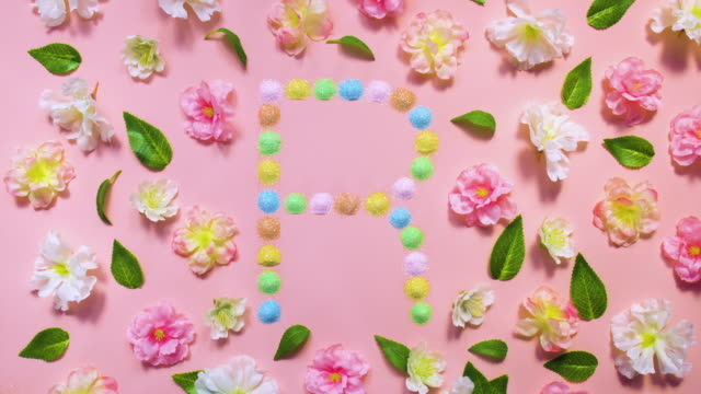 Sparkling Letter R- exploding multi pastel colored glitter powder surrounded by cherry blossoms and leaves on pastel pink background