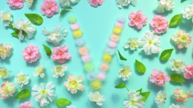 stockvideo's en b-roll-footage met sparkling letter v- exploding multi pastel colored glitter powder surrounded by cherry blossoms and leaves on pastel green background - bloemblaadje