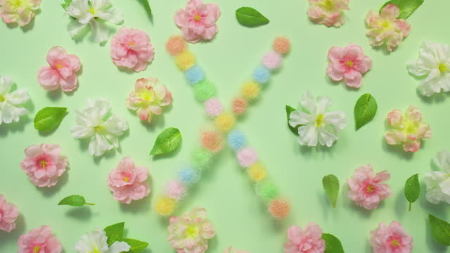 sparkling letter x- exploding multi pastel colored glitter powder surrounded by cherry blossoms and leaves on pastel green background - letter x stock videos & royalty-free footage