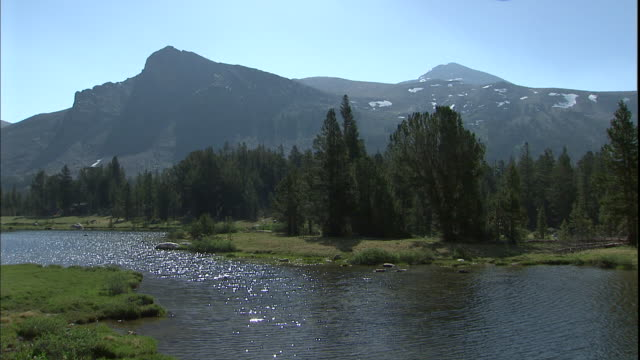 A sparkling river ripples at the base of tall mountains.