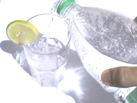 vídeos y material grabado en eventos de stock de agua cristalina vertido en vidrio - gaseosa