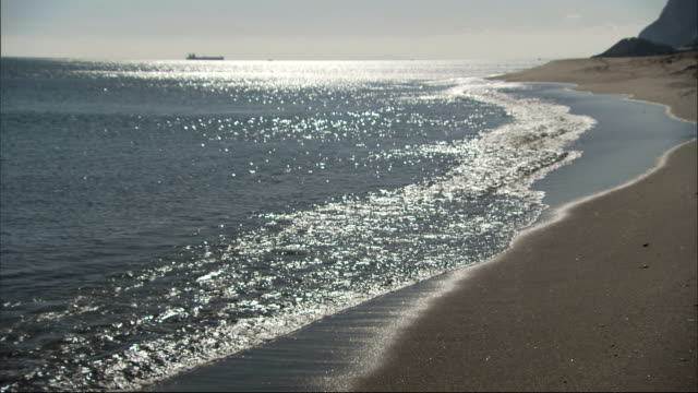 Sparkling waves wash onto a rugged shore on Gibraltar. Available in HD.