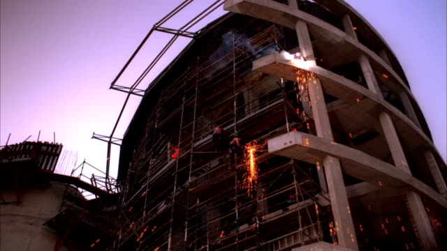 Sparks fall as construction workers weld the outside frame of a modern skyscraper. Available in HD.