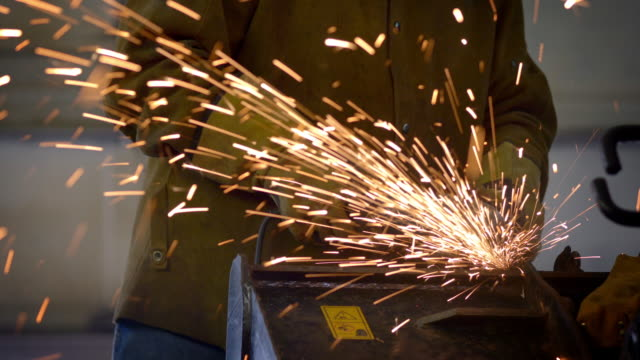 sparks fly as a man grinds heavy equipment in a repair shop - metallindustrie stock-videos und b-roll-filmmaterial