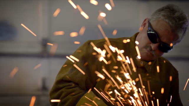sparks fly as a man grinds heavy equipment in a repair shop - steel worker stock videos & royalty-free footage