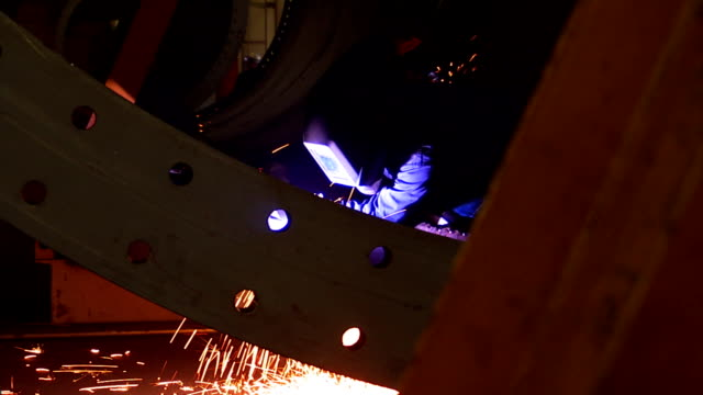 sparks fly as a welder uses an arc welder in a confined space. - welding helmet stock videos & royalty-free footage