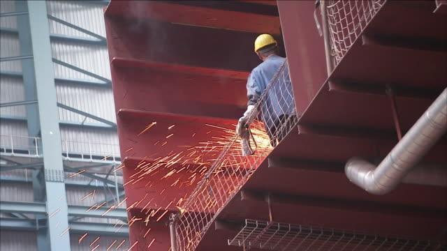 sparks fly as an employee welds in a warehouse. - 倉庫作業員点の映像素材/bロール