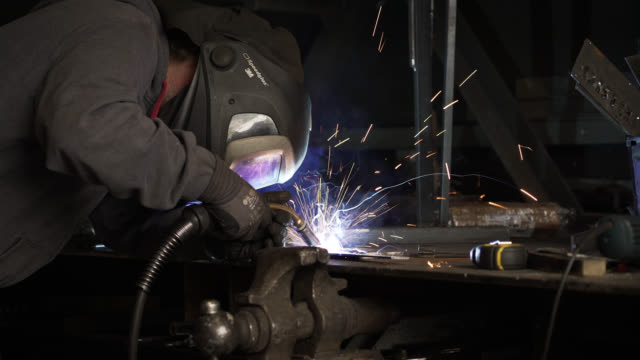 sparks fly as man welds metal on workbench - iron metal stock videos & royalty-free footage