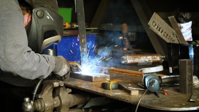 vídeos de stock e filmes b-roll de sparks fly as man welds metal with welding torch - ferro metal