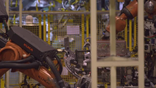 Sparks fly as robotic arms manufactured by Kuka AG work on the door of Trumpchi brand vehicles on a production line at the Guangzhou Automobile Group...