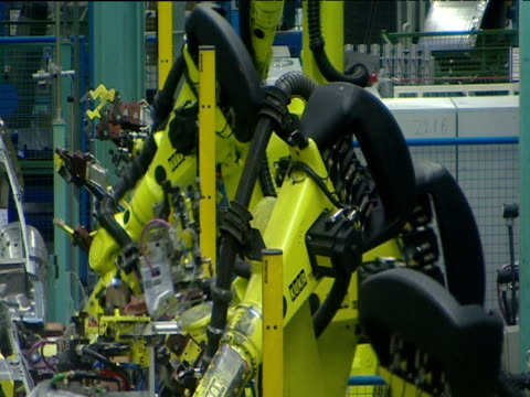 Sparks fly as robotic arms punch rivet chassis on car factory automated production line