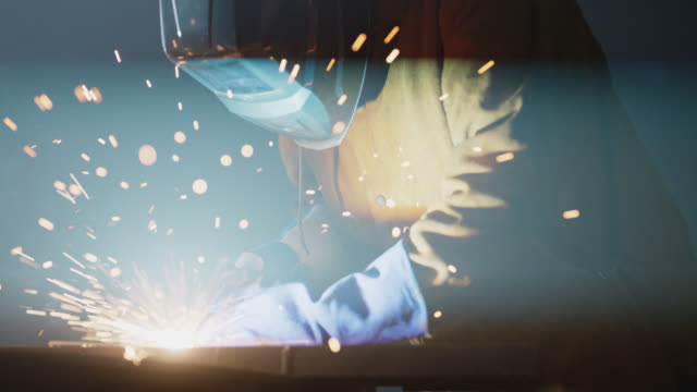 stockvideo's en b-roll-footage met slo mo cu sparks fly as skilled welder uses torch to join pieces of metal - metaalindustrie