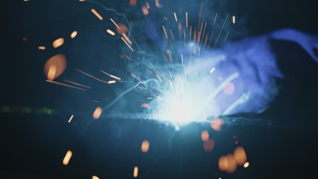 vidéos et rushes de slo mo cu sparks fly in the air as welding torch connects with metal - matériau