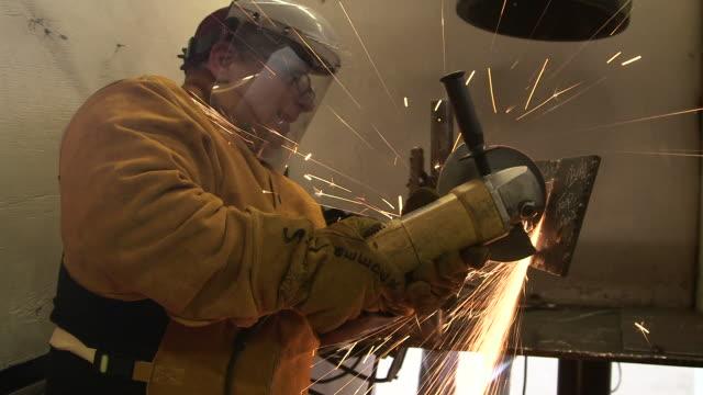 Sparks fly man uses grinder on metal