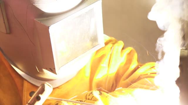 sparks fly, man uses welder - atemhilfe stock-videos und b-roll-filmmaterial