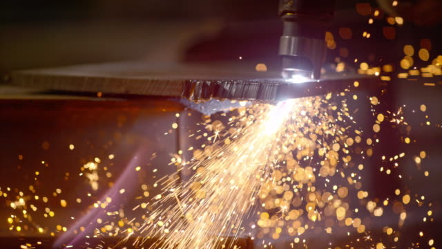 vídeos de stock, filmes e b-roll de slo mo pan sparks flying as worker cuts metal - ferro metal