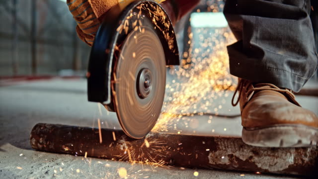vídeos de stock e filmes b-roll de slo mo ld sparks flying from angle grinder cutting a metal pipe - obra