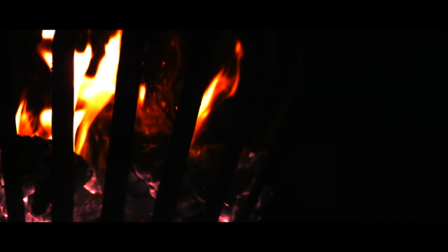 Sparks flying from fire in brazier, black background