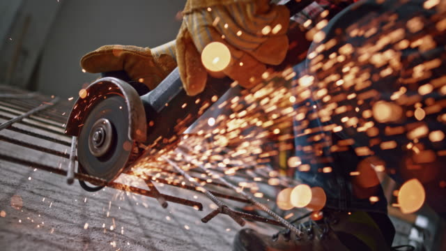 vídeos de stock e filmes b-roll de slo mo ld sparks flying from the disc of the angle grinder cutting steel - obra