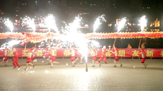 sparks of molten steel dash in all directions.the men perform a dragon dance to celebrate the spring festival of china. - dragon stock videos & royalty-free footage