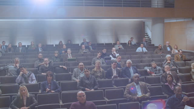 a sparse audience sits in a lecture hall. - hörsaal stock-videos und b-roll-filmmaterial