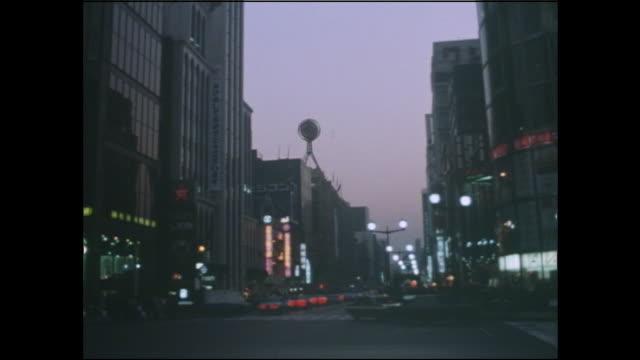 vídeos de stock, filmes e b-roll de sparse neon lights illuminate the ginza to save power during the oil crisis. - 1973