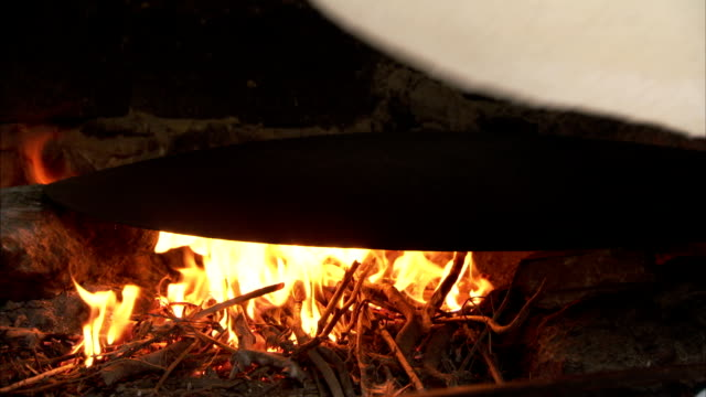 a spatula is used to unfold dough onto a hot plate over an open flame. - tortilla flatbread stock videos & royalty-free footage