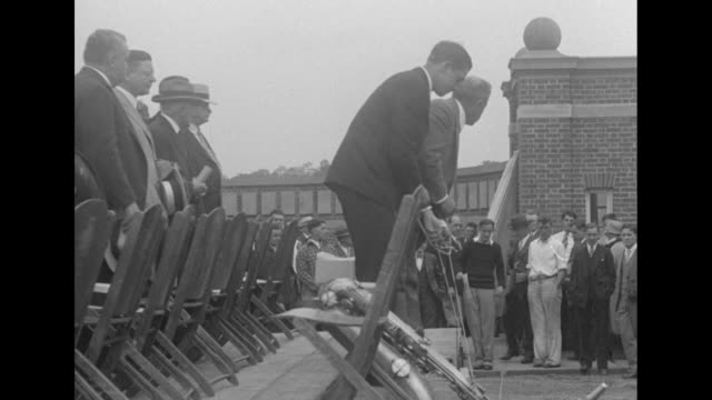 a speaker and people seated at iron fence at bucknell university / christy mathewson jr shakes hands with president john heydler of the national... - plakette stock-videos und b-roll-filmmaterial